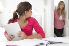 La mère attrape la fille à l'aide de la tablette une fois signifiée étudier Image libre de droits