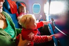 La mère avec des enfants voyagent en avion, voyage de famille photo stock