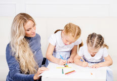 La mère avec deux belles filles dessinent Photographie stock libre de droits