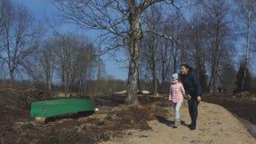 La mère avec la fille font une promenade près du lac banque de vidéos