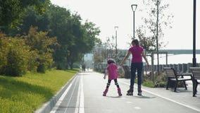La mère avec la fille vont sur des patins de rouleau clips vidéos