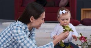 La mère avec l'arrangement de bébé s'est levée des fleurs à la maison banque de vidéos