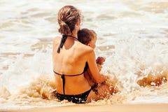 La mère avec l'enfant jouant en mer ondule Photographie stock