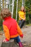 La mère avec l'enfant s'asseyent sur des moignons en bois Photos libres de droits