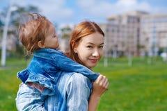 La mère avec l'enfant sur le sien soutiennent dehors Image libre de droits