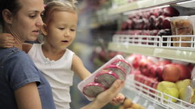 La mère avec la petite fille fait des achats dans le supermarché