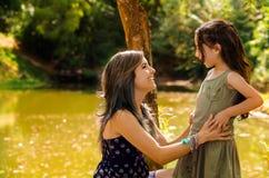 La mère avec la petite fille s'est habillée dans summerly habille poser heureusement l'embrassement pour l'appareil-photo, petit  Photos stock