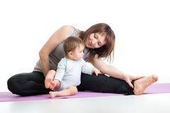 La mère avec le bébé faisant la gymnastique et la forme physique s'exerce Photo stock