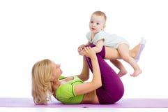 La mère avec le bébé font des exercices de forme physique Images stock