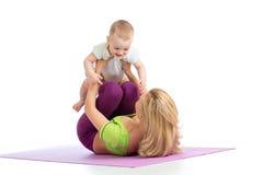 La mère avec le bébé font des exercices de forme physique Photographie stock libre de droits