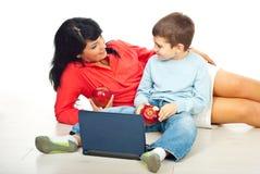 La mère avec le fils mangeant des pommes et discutent Photos libres de droits