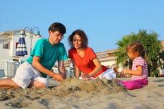 La mère avec le père et la fille s'asseyent sur la plage photo libre de droits