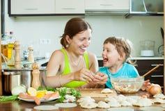 La mère avec sa fille fait des boulettes de viande de poissons dans la maison Image libre de droits