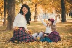 La mère avec son fils et fille joue en parc sur les feuilles Photo stock