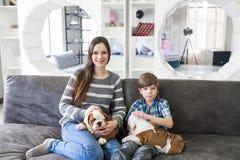 La mère avec son fils s'asseyant sur le divan et gardent le chiot anglais de bouledogue Photos stock