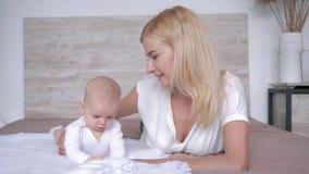 La mère avec son mensonge de détente de fille nouveau-née sur le lit, parent embrasse doucement sa fille banque de vidéos