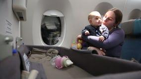 La mère avec très appliqué du petit enfant du premier vol sur l'avion, une femme tient le bébé infantile dans ses bras, étreintes clips vidéos