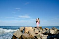 La mère avec un enfant sur les mains sur le bord de mer sont parmi les pierres Photographie stock
