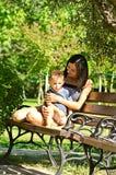 La mère avec un fils s'asseyent sur un banc Photographie stock