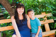 La mère avec un fils s'asseyent sur un banc dans un jardin Photos stock