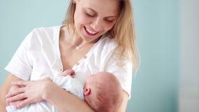 La mère berce doucement un bébé nouveau-né Amour maternel et soin Calme et frotte le bébé sur la tête la fleur de jour donne à de banque de vidéos