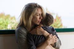 La mère blonde étreint son garçon de brune avec amour profond Photo stock
