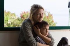 La mère blonde sourit et tient son enfant en bas âge entre ses bras Images libres de droits