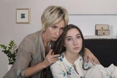 La mère calme la fille pleurante dans un lit images stock