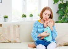 La mère calme le fils pleurant de bébé photographie stock libre de droits