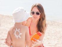 La mère caucasienne a fait le soleil avec le suncream à son fils sur la plage Photographie stock libre de droits