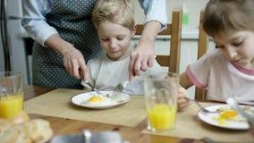 La mère a coupé les oeufs scruble pour le fils pendant le dîner de famille banque de vidéos