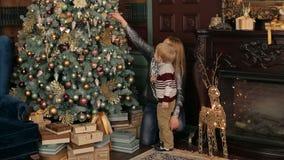 La mère décore de son petit arbre de Noël de fils banque de vidéos