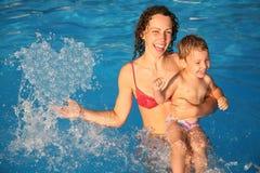 La mère dans l'eau avec l'enfant effectue le coeur avec des baisses Photographie stock libre de droits