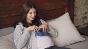 La mère de attente espiègle est les chaussures de bébé bleu de marche sur son ventre enceinte et mensonge de sourire sur le lit à banque de vidéos
