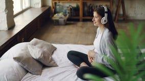 La mère de attente heureuse caresse son ventre et écoute la musique par des écouteurs se reposant sur le double lit dans gentil banque de vidéos