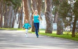 La mère de famille de sports et la fille d'enfant sont occupées à courir a Photos libres de droits