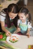 La mère de famille et la fille heureuses d'enfant préparent la nourriture saine, ils improvisent ensemble dans la cuisine Photographie stock libre de droits