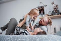La mère de famille, le père et la fille heureux d'enfant rit dans le lit photo stock