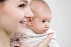 La mère de jeune femme dans des combinaisons de denim tient un enfant de bébé dans des ses bras Fond blanc dans le studio images stock