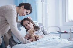 La mère de soin donnant une peluche jouent à la fille malade se situant dans des hos Photos stock
