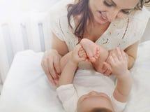 La mère de soin heureuse admirent les auriculaires de son bébé garçon mignon image stock