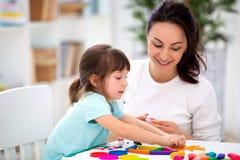 La mère de sourire aide une petite fille à sculpter des figurines de pâte à modeler Créativité du ` s d'enfants Famille heureux photo libre de droits