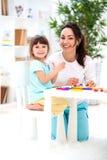 La mère de sourire aide une petite fille à sculpter des figurines de pâte à modeler Créativité du ` s d'enfants Famille heureux photographie stock