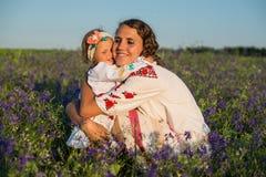 La mère de sourire et la petite fille sur la nature dans un domaine des pavots, fille tient des fleurs Images stock