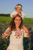La mère de sourire et la petite fille sur la nature dans un domaine des pavots, fille tient des fleurs Image stock