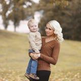 La mère de sourire heureuse de portrait se tenant dessus remet l'enfant en automne chaud photographie stock