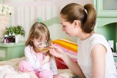 La mère donne à la boisson à l'enfant malade images libres de droits