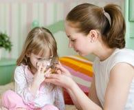 La mère donne à la boisson à l'enfant malade photographie stock libre de droits