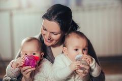 La mère donne les bouteilles de bébés jumelles image stock