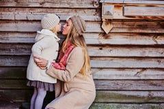 La mère a embrassé sa fille à la maison en bois image stock
